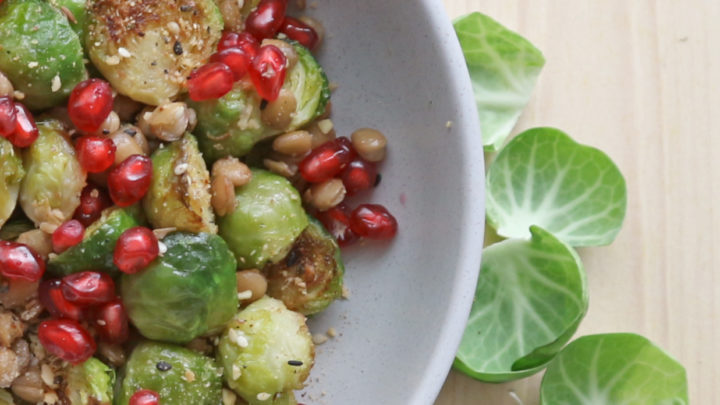 Roasted Brussel sprouts, green lentils, pomegranate seeds in a grey bowl with some raw Brussel Sprout outer leaves on a wooden board.