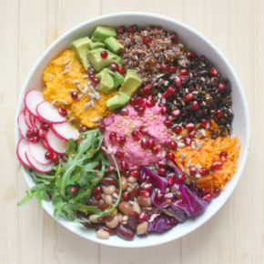 Bowl containing radish, avocado, quinoa, beetroot hummus, rocket, grated carrot and sprinkled with pomegranate seeds.